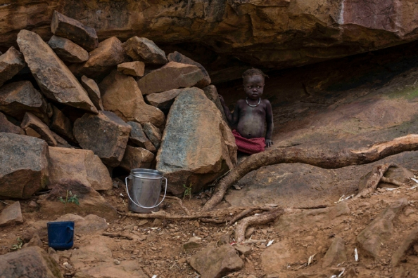 A young girl is standing outside the cave her and her family are staying in.
